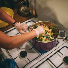 Widok z góry na gazową kuchenkę, na której stoi garnek wypełniony pokrojonymi warzywami i ziołami, widać ręce osoby, która miesza produkty w garnku