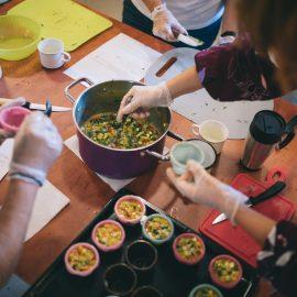 Widok z góry na kuchenny blat, na którym stoi garnek z warzywnym farszem oraz blaszkę do babeczek, widać ręce osób, które przekładają farsz do foremek