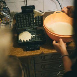 Widok na gofrownicę oraz miskę z ciastem na gofry