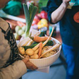 Osoba trzyma miskę z warzywami i owocami