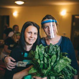 Dwie osoby stoją obok siebie pozuja do zdjęcia, jedna trzyma zielone liście szpinaku w ręce