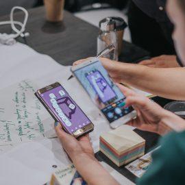 Zdjęcie, widok zza placów kobiety, która wyświetla na dwóch telefonach fioletowe grafiki.