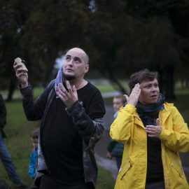 Łysy mężyczyzna pokazuje ręką niewidoczny na zdjęciu punkt na niebie, stojąca obok niego kobieta tłumaczy jego słowa na Polski Język Migowy. Mężczyzna ubrany jest w czarną bluzę, kobieta w żółtą kurtkę przeciwdeszczową.