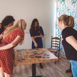 Grupa młodych kobiet stoi dookoła małego, drewnianego stołu i ogląda rozłożone na nim pocztówki. Nie widać szczegółów na pocztówkach. Kobiety ubrane są na letnią porę roku.