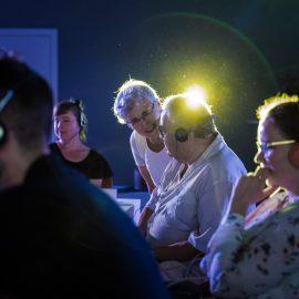 Grupa osób siedzi w pomieszczeniu, każda osoba ma założone słuchawki. Na pierwszym planie widać młodego, krótko ściętego mężczyznę, obok niego siedzi młoda kobieta w okularach. Zaraz obok nich widać parę starszych osób - kobieta stoi nad mężczyzną i mówi do niego. Oboje są uśmiechnięci. Nad głową mężczyzny świeci bardzo jasna, żółta lampa, która oświetla całą scenę.