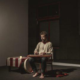 Mężczyzna siedzi w ciemnym pomieszczenu na krześle. Nie ma butów, ubrany jest w szarą koszulę i jeansy. Na kolanach trzyma instrument, na którym gra. Obok niego jest stolik z białoczerwonym obrusem i świecą.