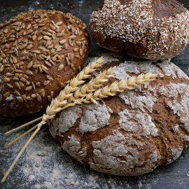 Okrągłe bochenki chleba leżące na szarej powierzchni. Na chlebach położone są dwa kłosy pszenicy
