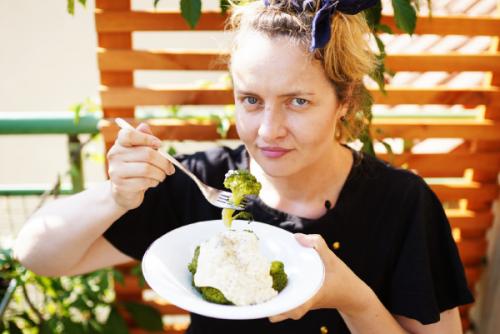 Zdjęcie, Aleksandra w trakcie jedzenia brokułów z białym sosem. Jest na zewnątrz i trzymając widelec patrzy się prosto w obiektyw.