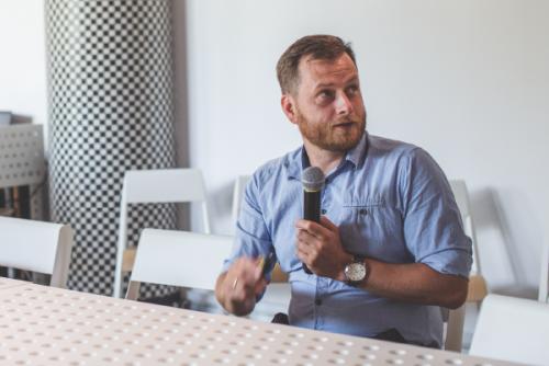 Zdjęcie, Tomasz siedzi przy stole w Barbarze. W ręku trzyma mikrofon i jest w trakcie rozmowy