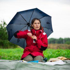 Zdjęcie kobiety siedzącej na kocu na trawie. Kobieta ma na sobie czerwoną kurtkę i w ręce trzyma parasolkę.