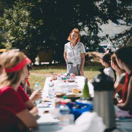 W scenerii plenerowej podwórka odbywają się zajęcia. Widok na stół warsztatowy oraz Agnieszkę - prowadząca spotkanie z wyplatania makram.