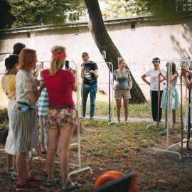 Widok na grupę osób biorących udział w warsztatach wyplatania makram. Uczestniczki i uczestnicy spotkania stoją przed wieszakami na ubrania, na których zostały zamocowane bawełniane sznurki. Osoby wyplatają ze sznurków wiszące kwietniki na doniczki.