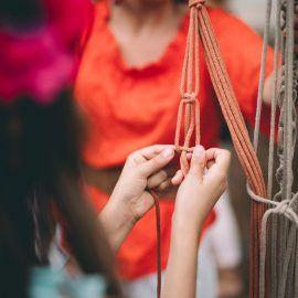 Zbliżenie na dłonie osoby wyplatającej z bawełnianego sznurka wiszący kwietnik na doniczkę.
