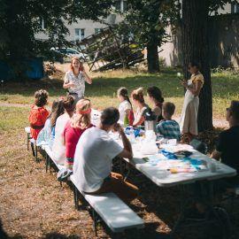 W scenerii plenerowej podwórka odbywają się zajęcia. Widok na stół warsztatowy oraz Agnieszkę - prowadząca spotkanie z wyplatania makram oraz uczestniczki i uczestników warsztatów.