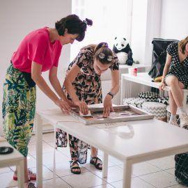 Zdjęcie przedstawia dwie osoby wykonujące nadruk metodą sitodruku. Osoby stoją przy stole, nachylając sie nad jego blatem, na którym rozłożony jest bawełniany fartuch oraz siatka, za pomocą której przenoszony jest obraz na tkaninę.