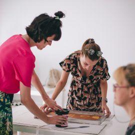 Na zdjęciu znajdują się trzy osoby. Jedna z nich siedzi przy stole, a dwie stoją przy nim. Osoby przy stole nachylają się nad rozłożoną na nim tkanina i siatką, przenosząc metodą sitodruku, przy pomocy farby, grafikę na powierzchnię materiału.