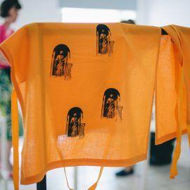 """Na zdjęciu widoczny jest pomarańczowy fartuch, na którego powierzchni zostały naniesione dziewczyna trzymająca przed sobą bawełniany fartuch. Fartuch został uszyty z tkanin z odzysku, ma on pomarańczowy kolor bez wzorów. Jest on bawełniany. Na jego powierzchnię zostały naniesione metodą sitodruku powielone grafiki przedstawiające element architektury jednego z budynków: rzeźbę kobiety oraz kolumnę. W górnej części fartucha znajduje się napis: """"frajer"""" znaleziony na murze jednego z budynków Przedmieścia Oławskiego. Napis i grafiki zostały naniesione na tkaninę przy pomocy farby w kolorze czarnym."""