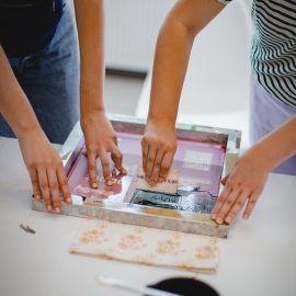 Zbliżenie na ręce osoby wykonującej nadruk metodą sitodruku. Osoba jedną ręką dociska siatkę do stołu i tkaniny, w drugiej ręce ma rakiel, czyli gumowy klocek służący do nanoszenia farby na tkaninę.