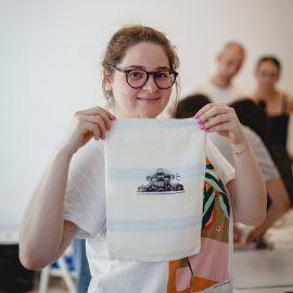 Zdjęcie przedstawia uśmiechniętą dziewczynę, która trzyma woreczek z własnoręcznie naniesioną grafiką.