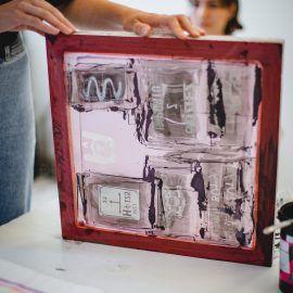 Zdjęcie przedstawia widok na siatkę w ramie. Na siatkę zostały naniesione grafiki, które nastepnie można odbijać na papierze lub tkaninie.