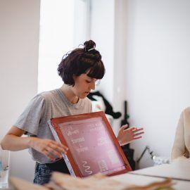 Zdjęcie przedstawia dziewczynę, która prowadzi warsztaty z sitodruku. Pokazuje ona specjalnie przygotowaną siatkę w ramie, Dzięki tej siatce możliwe jest przenoszenie znajdującego sią na niej wzoru na inne materiały.