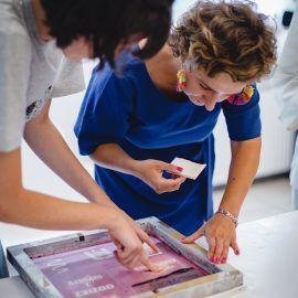 Zdjęcie przedstawia osoby biorące udział w warsztatach, które nachylają się nad siatką dopasowując wzór, który chcą przenieść na tkaninę.
