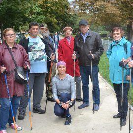 Zdjęcie grupowe przedstawiające uczestników i uczestniczki plenerowego spotkania nordic walking. Osoby na zdjęciu trzymają w rękach kije do maszerowania.