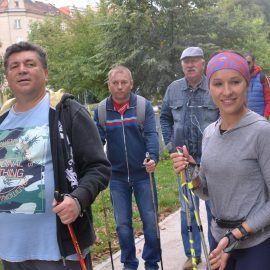 zdjęcie wykonana w trakcie spotkania sportowego - nauki maszerowania z kijami. Uczestnicy spotkania mają w rękach kije do Nordic Walking.