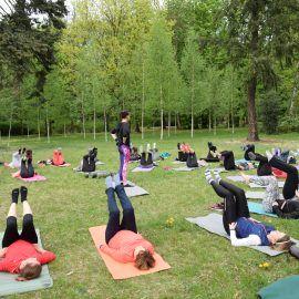 Grupa osób ćwiczy w parku. Leżą na matach i trzymają nogi w górze. Pomiędzy nimi stoi prowadząca