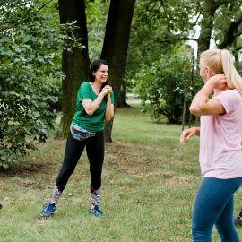 Cztery kobiety ćwiczą w parku. Rozciągają mięśnie rąk. Wszystkie są uśmiechnięte - widać, że treningi sprawiają im dużo radości