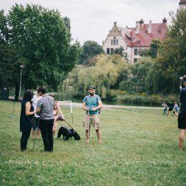 Grupa osób stoi na trawniku - pogrupowani są w pary składające się z osoby z niepełnosprawnością wzroku i osoby widzącej. Grupa rozmawia ze sobą.