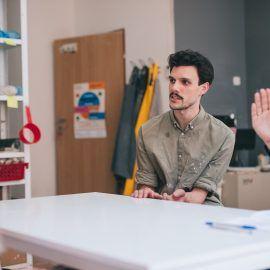 Widok na osoby prowadzące warsztaty ceramiczne oraz osobę tłumaczącą spotkanie na Polski Język Migowy.
