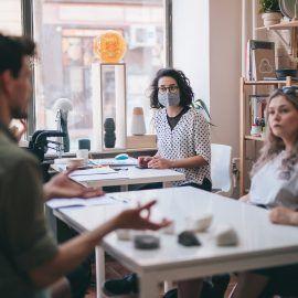 Zdjęcie wnętrza pracowni ceramicznej Zakwas Studio. Widok na osoby biorące udział w warsztatach. Osoby siedzą przy stole, na którym znajdują się przedmioty ceramiczne.