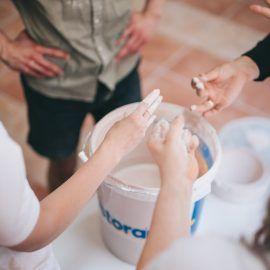 Zbliżenie na ręce osób biorących udział w warsztatach. Widok z góry na wiaderko ze szkliwem, w którym osoby zanurzają swoje prace.