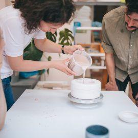 W pracowni ceramicznej dwie osoby nachylaja się nad stołem wlewając masę do formy odlewniczej, z której powstanie ceramiczny kubek.