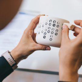 Zbliżenie na ręce osoby biorącej udział w warsztatach. Osoba trzyma w rękach kubek ceramiczny, który ozdabia metodą stemplowania wzoru na powierzchni naczynia.