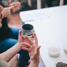 Zdjęcie dłoni trzymających błękutny ceramiczny kubek wykonany w pracowni Zakwas Studio.