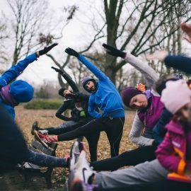 Grupa osób rozciąga się w plenerze - każda z nich trzyma nogę na ławce i pochyla się do niej rozciągając mięśnie ud.