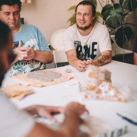 Widok na uczestników i uczestniczki spotkania w pracowni ceramicznej. Na stole widać glinę, z której formowane są ceramiczne przedmioty.