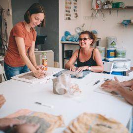 Widok na dwie uczestniczki pracujące nad swoimi naczyniami z gliny. Jedna z nich stoi przy stole, druga siedzi.