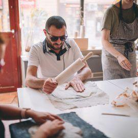 Widok na jednego z uczestników spotkania. Siedzi on przy stole przodem do osoby fotografującej. W jednej ręce trzyma wałek. Drugą dłonią wyrównuje kawałek rozwałkowanej gliny.