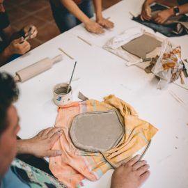 Zbliżenie na stół i dłonie uczestników wykonujących swoje ceramiczne prace.