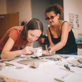 Na zdjęciu zrobionym w pracowni ceramicznej widać dwie dziewczyny, które ozdabiają farbami swoje prace.