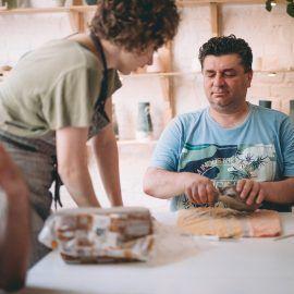 Na zdjęciu uczestnik ceramicznych warsztatów - Pan Marek - wykonuje z gliny przedmiot, który następnie zostanie wysuszony, pomalowany i wypalony w piecu, tak by nadawał się do codziennego użytkowania.