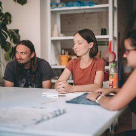 Widok na uczestników i uczestniczki spotkania trakcie wykładu w pracowni ceramiczne. Osoby siedzą przy stole. W tle widać regał, na którym znajdują się wykonane prace.